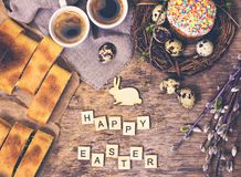 Easter table. Easter table decoration, pies, eggs, Easter cake, rabbit, seals, spring bouquet. Easter still life. The inscription 'Happy Easter royalty free stock photography