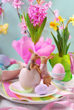 Easter table decoration with rabbits and spring flowers Stock Photo