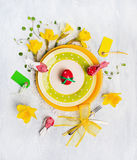 Easter table decoration with red egg, spring flowers, sign, knife and fork on yellow plate Royalty Free Stock Photo