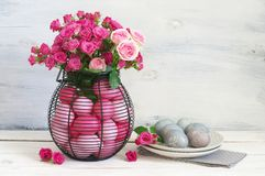 Easter table decoration. Varicolored pink Easter eggs in wire basket with roses bouquet, grey eggs in plate and napkin on rustic white wooden background. Table Royalty Free Stock Photos
