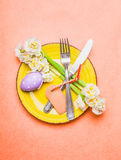 Easter table place setting with daffodils flowers, cutlery, plate, eggs and empty label card on pastel pink background, top view stock photography