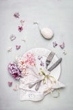 Easter table place setting with decor egg, plate, cutlery, napkin, ribbon and beautiful pastel pale hyacinths  flowers, top view Royalty Free Stock Images