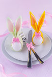 Easter table set with eggs in bunny napkins. Easter eggs wrapped as bunnies on plate with silverware for menu Stock Photos