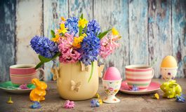 Easter table setting. Easter breakfast table with tea,eggs in egg cups, spring flowers in vase and Easter decor Stock Photo