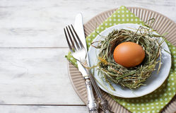 Easter table setting with chicken eggs in nest Stock Photo
