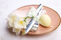 Easter laying table appointments, table setting options. Silverware, tableware items with festive decoration. Fork, knife and flow. Easter table setting Stock Photos