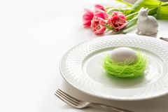 Easter table setting with pink tulip on white. Spring romantic dinner. Space for text. Easter table setting with pink tulip on white. Spring romantic dinner royalty free stock photography