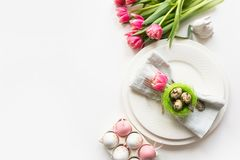 Easter table setting with pink tulip on white. Spring romantic dinner. Top view and space for text. Easter table setting with pink tulip on white. Spring royalty free stock photo