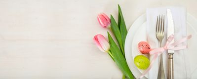 Easter table setting with pink tulips on white wooden background. Top view, copy space, banner Royalty Free Stock Photography