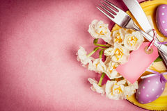 Easter table setting with plate, cutlery, flowers ,eggs and blank tag on pink background, top view Stock Images