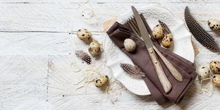 Easter table setting with quail eggs. And feathers Stock Photos