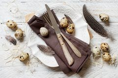 Easter table setting with quail eggs. And feathers Royalty Free Stock Photography
