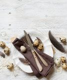 Easter table setting with quail eggs. And feathers Stock Photo