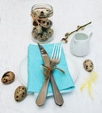 Easter table setting. Quail eggs, plate on a old white wooden background Stock Photos