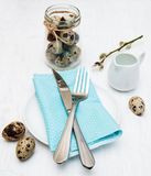 Easter table setting. Quail eggs, plate on a old white wooden background Stock Photography
