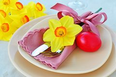 Easter table setting with red dyed egg. Simple table setting arrangement with cream porcelain dishes, red Easter egg, yellow daffodil flower, cutlery and napkin Stock Photography
