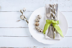 Easter table setting with spring flowers, eggs and cutlery. Holidays background with quail eggs, white plate, cutlery, napkin, ribbons and willow on light stock images