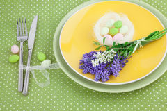Easter Table Setting with Spring Flowers on Green Polka Dot Tablecloth Royalty Free Stock Photo