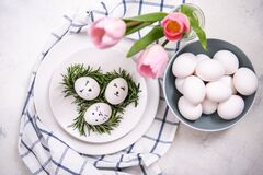Easter table setting with white eggs in a nest, on a blue and white checkered napkin. Nearby are pink tulips. Faces are painted on