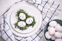 Easter table setting with white eggs in a nest, on a checkered napkin. Faces are painted on the eggs. Top view, flat lay