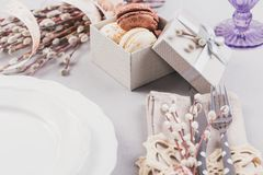 White plate, purple glass, cutlery, present box with macaroons and willow twigs royalty free stock images