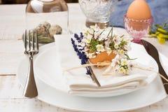 Easter table setting, white plates, napkin, flowers in eggshell, lavender, quail eggs, minimalistic Royalty Free Stock Photos