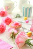 Easter table with sweet eggs, pink roses Royalty Free Stock Images