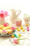 Easter table with sweet eggs, pink roses and fresh cakes Stock Image