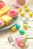Easter table with sweet eggs, pink roses and fresh cakes Royalty Free Stock Photo