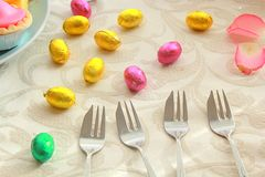 Easter table with sweet eggs and silver forks Stock Photography