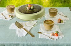 Easter table with tea matcha cheesecake and white coffee on background of green grass Stock Image