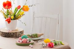 Easter table with tulips and decorations. In white interior royalty free stock images