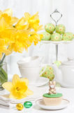 Easter Tea Party. Festive Easter table setting with freshly picked spring daffodils and bunny cupcake Stock Photo