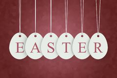 Easter text on egg shape hanging labels Royalty Free Stock Photo
