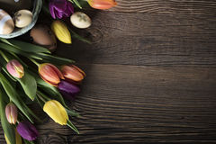 Easter theme. Bouquet of tulips.   Easter eggs. Colorful bokeh, place for typography and logo. Rustic wooden table Stock Photo