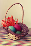 Easter theme. Easter colored eggs in a small basket stock images