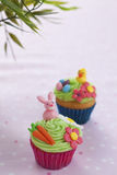 Easter themed cupcakes. Pair of easter themed cupcakes with rabbit, eggs, chick and flowers Royalty Free Stock Photos