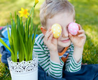 Easter time. Cheerful positive little boy holding colorful eggs at easter time Stock Photos