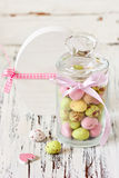 Easter time. Sweet chocolate eggs in a glass jar and Easter decorations on a white wooden board stock photos