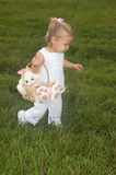 Easter Time. Adorable Little Girl walking with Bunny Rabbit Easter Basket Looking for Eggs Stock Images