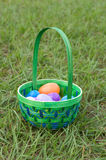 Easter Time. Easter basket filled with plastic eggs in the grass Stock Photos