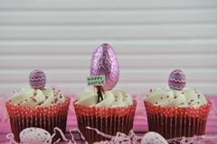 Cupcakes topped with a miniature person figurine holding a sign for happy Easter with egg decorations. Easter time decorations of chocolate wrapped pink eggs royalty free stock photography