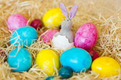 The Easter toy Bunny is hatching of the egg. Among the colorful eggs on hay Royalty Free Stock Image