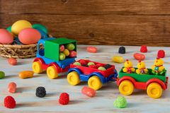 Easter toy car with trailer and color sweets in, Easter eggs and candy on wooden background. Color Easter sweets in toy track and trailers next to Color Easter Stock Photography