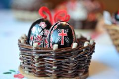 Easter traditional eggs black and red in a woven basket. Easter traditional eggs black and red in a woven basket on white and red background Royalty Free Stock Image