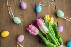 Easter traditional objects on dark wooden background colorful eggs and tulips stock photography