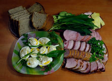Easter treats. Homemade sausages, pork belly and bacon with greens and eggs under horseradish Royalty Free Stock Photo