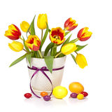 Easter tulip flowers. Spring tulip flowers in a white pot with easter eggs isolated on white royalty free stock images
