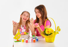 Easter - Two girls, basket with eggs, paint for coloring and a vase of flowers Stock Image