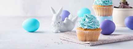 Easter vanilla cupcakes, colored eggs, cute bunny and hyacinth stock images